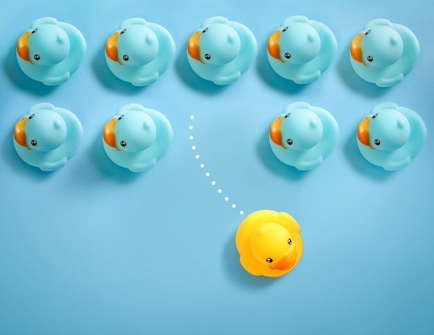 Grupo de patos de juguete azules flotando en una dirección y un pato de juguete amarillo flotando de manera diferente en azul.