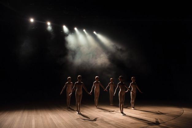 Un grupo de pequeñas bailarinas de ballet ensaya en el escenario con luz y humo.