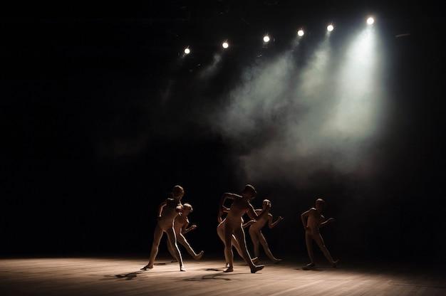 Un grupo de pequeños bailarines ensaya en el escenario con luz y humo.