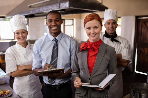 Grupo de personal del hotel de pie en la cocina