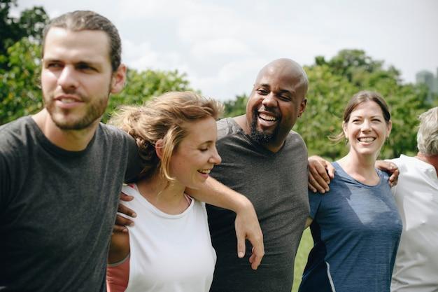 Grupo de personas abrazándose en el parque.