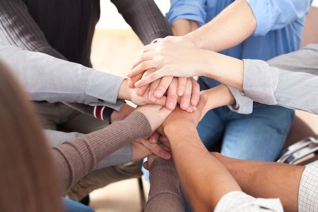 Grupo de personas apilando las manos juntas