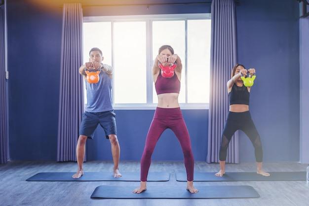 Grupo de personas aptas que sostienen la campana de la caldera durante una clase de ejercicios en el gimnasio.