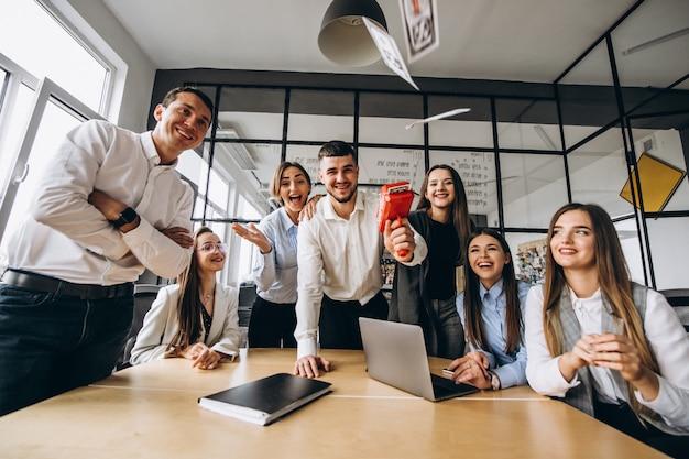 Grupo de personas arrojando dinero en una oficina