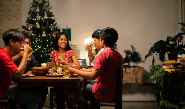Grupo de personas asiáticas cenan y beben cerveza en casa