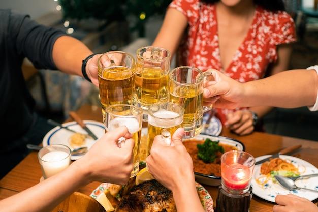 Grupo de personas asiáticas tienen una cena y cerveza en casa. tintinean un vaso de cerveza.