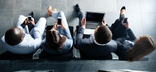Grupo de personas atractivas jóvenes sentados en las sillas usando una computadora portátil, tablet pc, teléfonos inteligentes, sonriendo