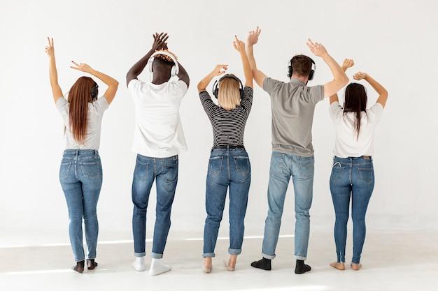 Grupo de personas con auriculares con la espalda