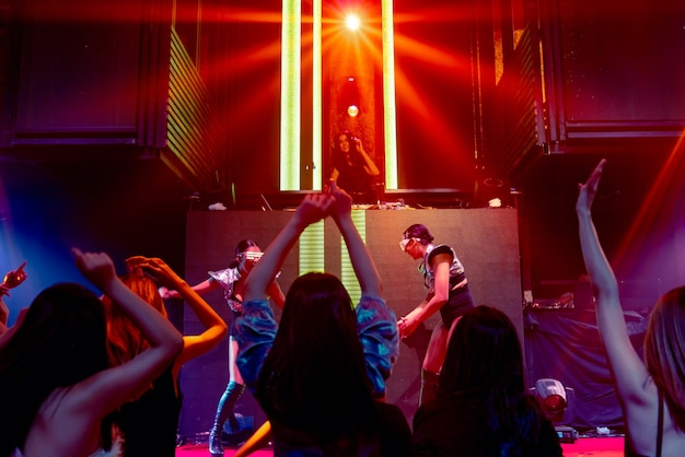 Grupo de personas bailan en la discoteca al ritmo de la música de dj en el escenario