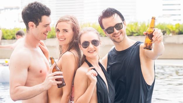 Grupo de personas en bikini nadando baile desnudo y fiesta en la piscina de agua con bebida de botella de cerveza.