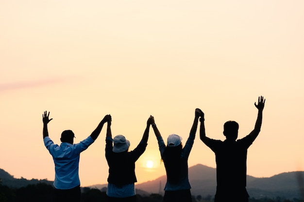 Grupo de personas con los brazos levantados mirando al amanecer en el fondo de la montaña. felicidad, éxito, amistad y conceptos comunitarios.