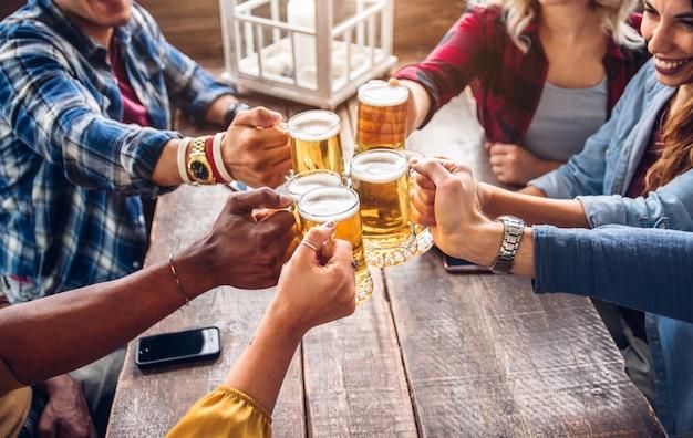 Grupo de personas brindando una cerveza en el pub cervecería