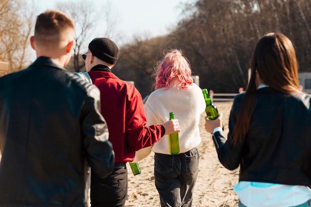 Grupo de personas caminando con botellas de cerveza