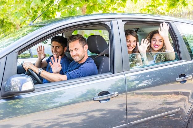 Grupo de personas en el coche agitando las manos.