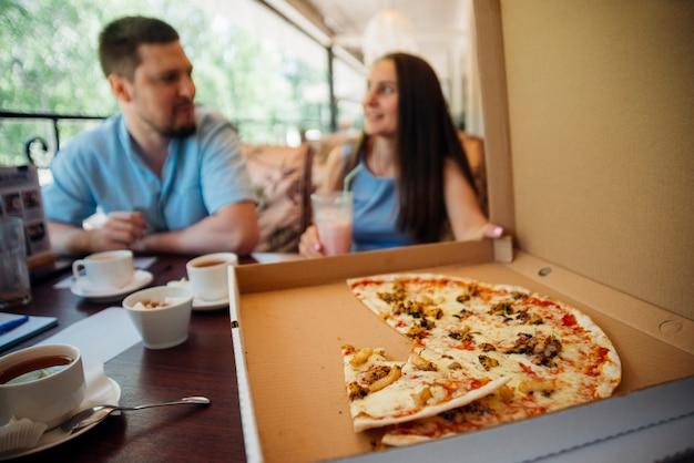 Grupo de personas comiendo pizza en café