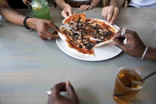 Grupo de personas comiendo pizza de cerca