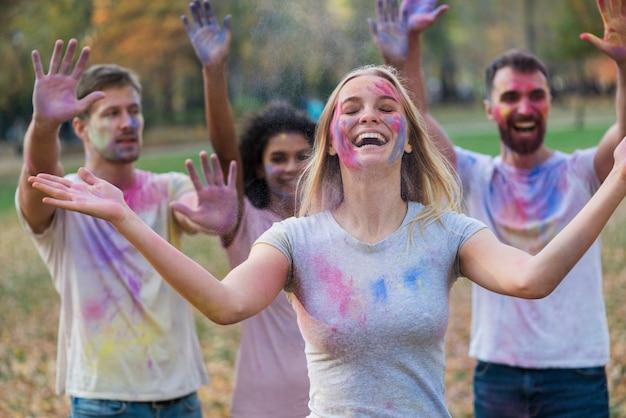 Grupo de personas cubiertas de pintura multicolor.