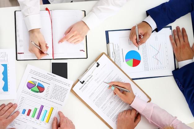 Grupo de personas discuten plan en primer plano de lugar de trabajo