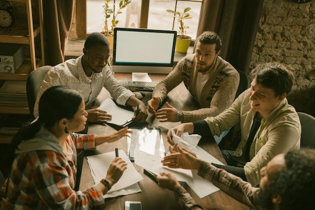 Grupo de personas discutiendo ideas en el espacio de coworking
