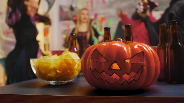 Grupo de personas con disfraces celebrando halloween y bailando. patatas fritas y cerveza para la fiesta.