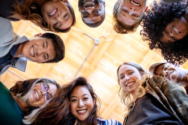 Grupo de personas diversas con caras sonrientes desde abajo ver