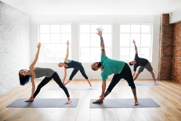 Grupo de personas diversas se están uniendo a una clase de yoga