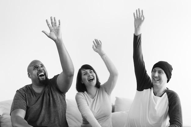 Grupo de personas diversas levantando sus manos