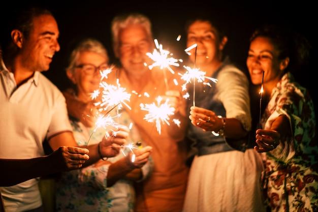 Grupo de personas se divierten celebrando junto con destellos.