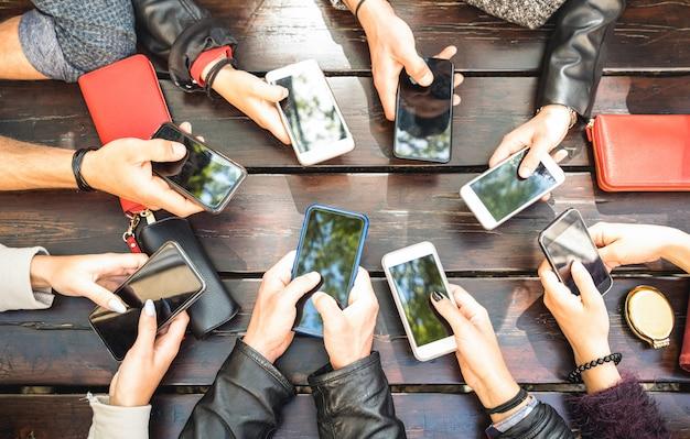 Grupo de personas divirtiéndose adictos juntos usando teléfonos inteligentes