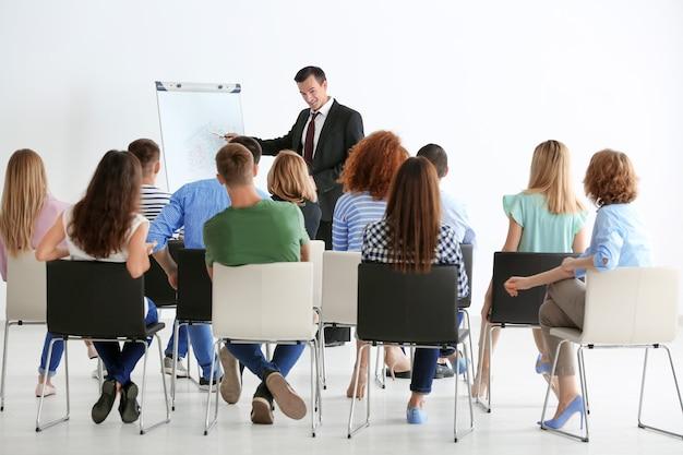 Grupo de personas con entrenador de negocios en seminario.