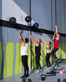 Grupo de personas de entrenamiento crossfit con bolas de pared y cuerda