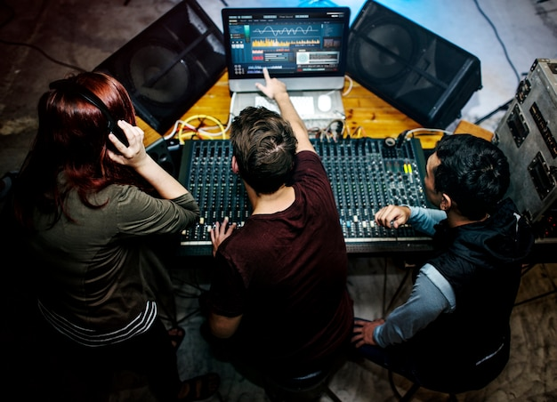 Grupo de personas en una estación mezcladora de sonido.