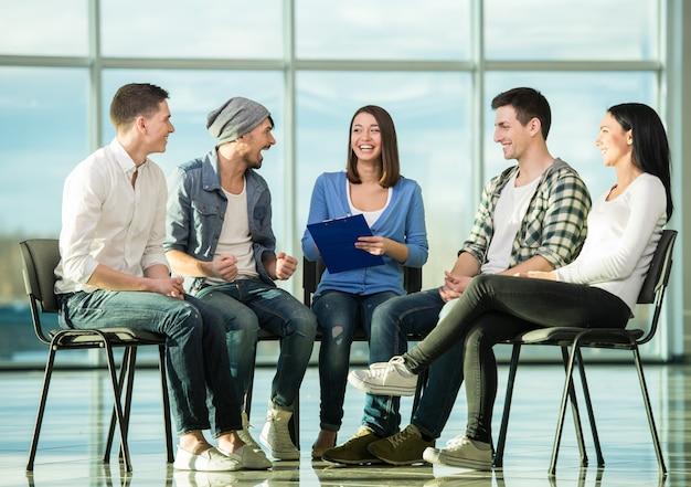 Grupo de personas están sentadas en círculo.