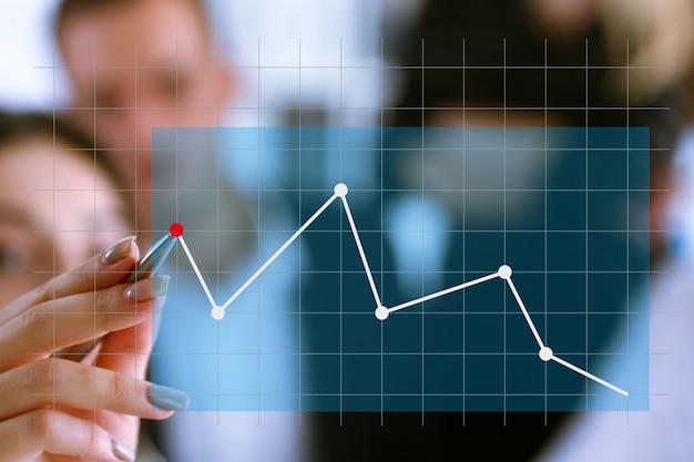 Un grupo de personas examina las estadísticas financieras de una empresa que señala con una mano con un bolígrafo el punto del gráfico.
