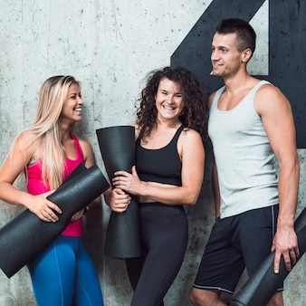 Grupo de personas felices con alfombra de fitness