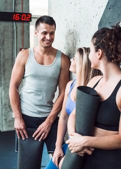 Grupo de personas felices con estera de ejercicio en el gimnasio