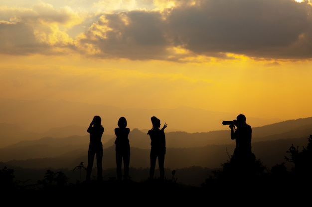 Grupo de personas felices fotografiando en la montaña al atardecer