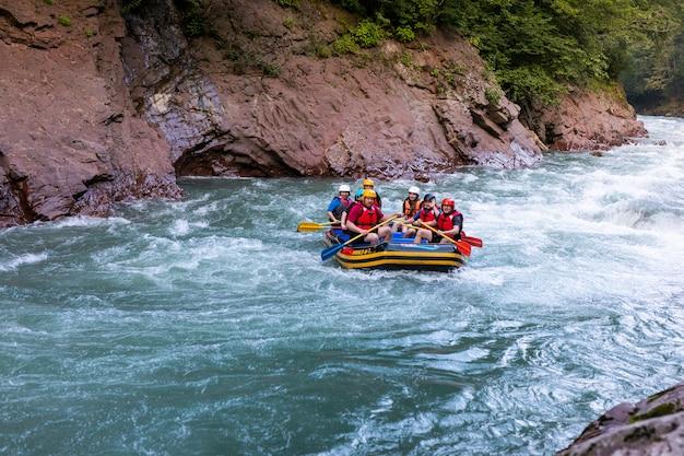 Grupo de personas felices con guía de rafting y remo en aguas bravas en el río.