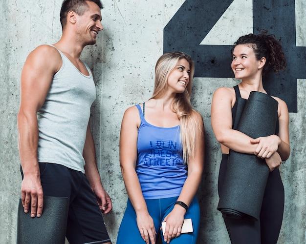 Grupo de personas felices de pie contra la pared en el gimnasio
