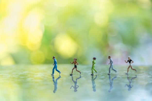 Grupo de personas figura miniatura corredor corriendo en el suelo con la naturaleza de la hoja verde.