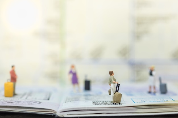 Grupo de personas de figura en miniatura de viajero con equipaje en pasaporte