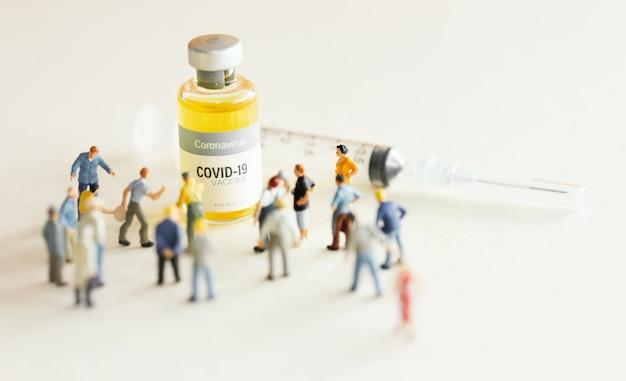 Grupo de personas (figurilla) que se oponen a la vacuna contra el coronavirus covid-19 y la jeringa para inyección .vacuna contra el coronavirus, fondo del concepto de campaña de inmunización de la población.