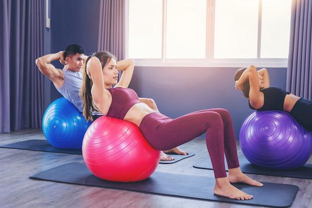 Grupo de personas en forma que trabajan en clase de pilates con bola de fitness