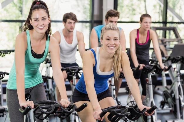 Grupo de personas en forma usando bicicleta juntos en el gimnasio