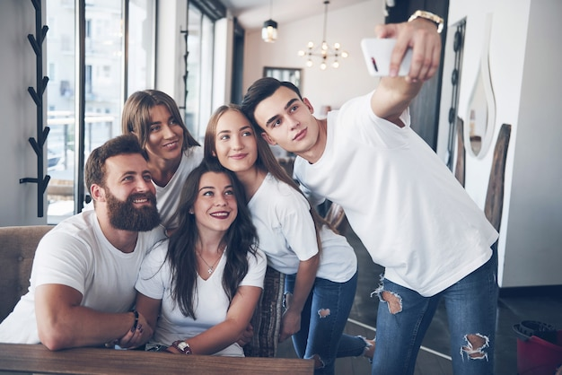 Un grupo de personas hace una foto selfie en un café. los mejores amigos se reunieron en una mesa para cenar comiendo pizza y cantando varios tragos.