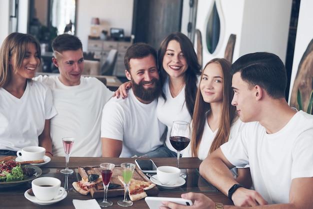 Un grupo de personas hace una foto selfie en un café. los mejores amigos se reunieron en una mesa para comer pizza y cantar varias bebidas.