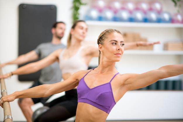Grupo de personas haciendo ejercicios de torsión espinal