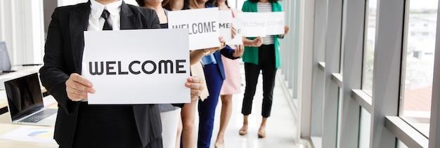 Grupo de personas irreconocibles se une saludando y sosteniendo palabras de bienvenida como señal de felicidad y placer por venir de algo o alguien.