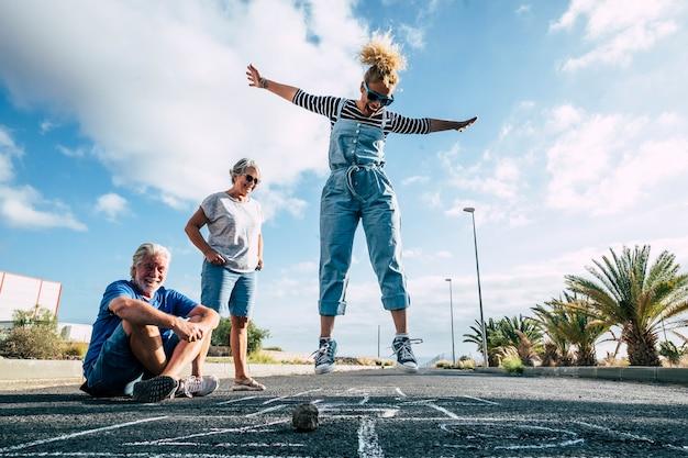 Grupo de personas jugando a la rayuela juntos en la calle sobre el asfalto - familia con una hermosa mujer y dos personas mayores - juego divertido juntos