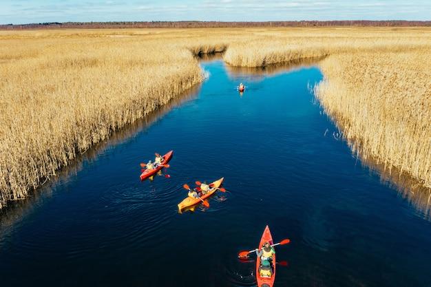 Grupo de personas en kayaks entre cañas en el río de otoño.